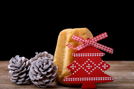 cone cake cone: pandoro cake with pine cone and red wooden christmas tree on wood