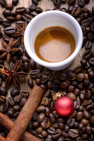 frijoles rojos: cup of coffee with coffee beans, cinnamon, star anise and red christmas ball on wood