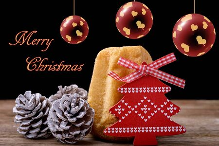 cone cake cone: pandoro cake with pine cone and red wooden christmas tree on wood and christmas balls and merry christmas written on black background