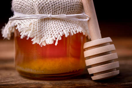 wooden stick: jar of honey and wooden stick to honey on wood Stock Photo