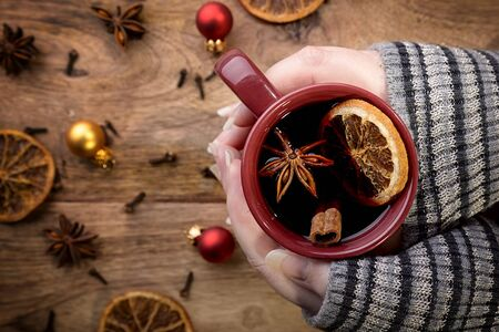 cinnamon stick: cup of mulled wine in female hands with orange, cinnamon stick, star anise, cloves and christmas balls