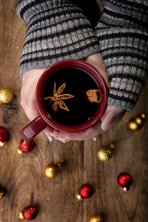 cinnamon stick: cup of mulled wine in female hands with cinnamon stick, star anise and red and gold christmas balls