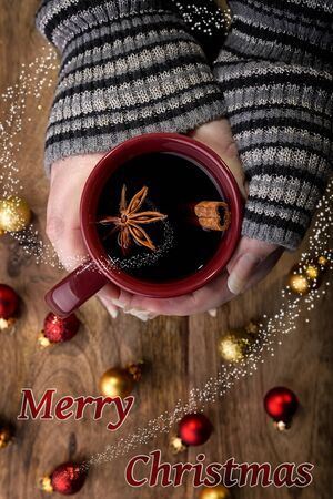 cinnamon stick: cup of mulled wine in female hands with cinnamon stick, star anise and red and gold christmas balls and merry christmas written and spiral snow Stock Photo