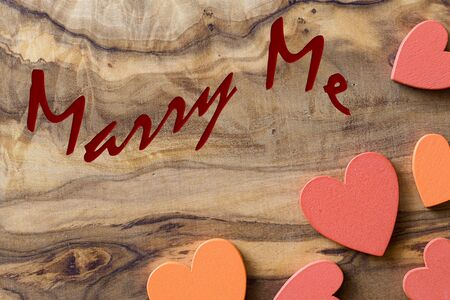 marry me: olive wood with wooden hearts and marry me written to celebrate love Stock Photo