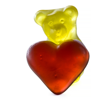 romantic background: gummy bear with red gummy heart isolated on white background