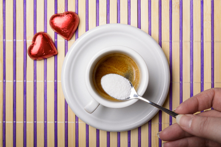 sweeten: female hand with a teaspoon of sugar to sweeten a cup of coffee and two chocolate heart Stock Photo