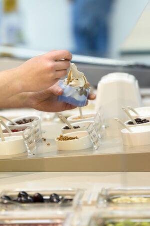serves: Woman prepares and serves a frozen yogurt with caramel