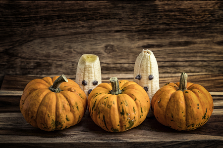 terrifying: Three pumpkins and ghosts made with banana and chocolate for halloween over wood Stock Photo