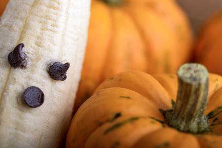terrifying: pumpkins and ghosts made with banana and chocolate for halloween over wood