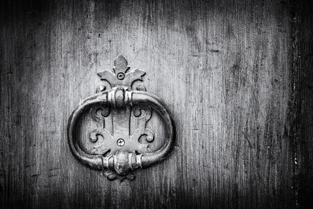 back gate: old handle of a wooden door with knocker black and white