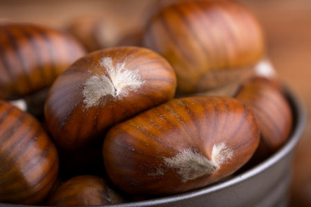 natures: macro heap of chestnuts in a tin bucket
