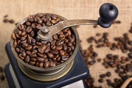 coffee beans in old coffee grinder on jute