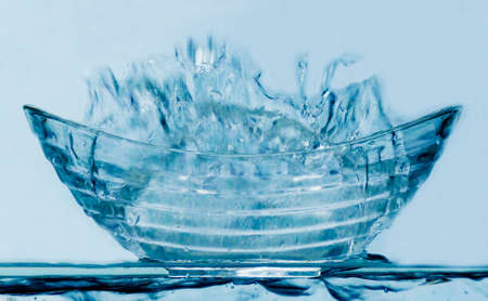 Liquid water splashing out of a blue glass bowl