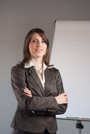 Young business woman standing in front of a flipchart photo