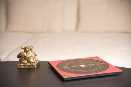 feng shui: An asian symbol and a Feng Shui compass on a table Stock Photo