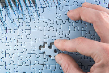 A Hand bringing two puzzle pieces together Stock Photo - 8597516
