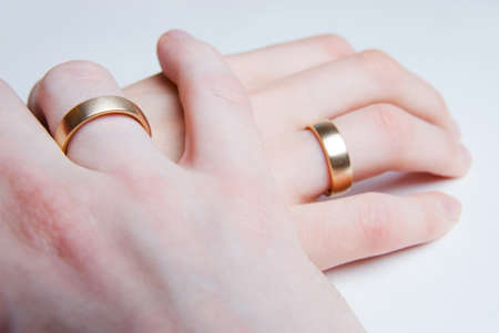 The hand of a man is gently holding the hand of a woman, both wearing golden wedding rings photo