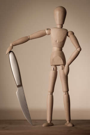 wood figurine: A wooden jointed doll with a shiny sharp knife.
