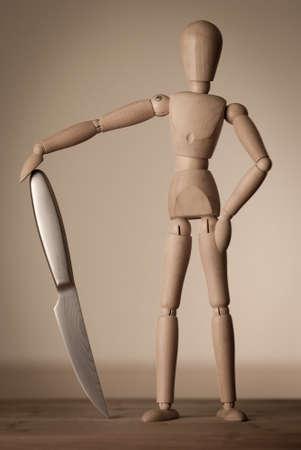 Eine hölzerne gelenkartigen Puppe mit einem glänzenden scharfen Messer.
