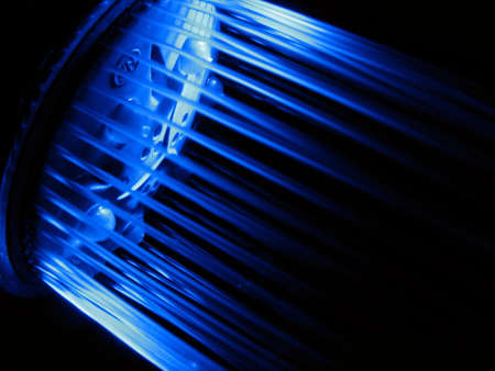 Stream of water from a shower at light of a dark blue light-emitting diode
