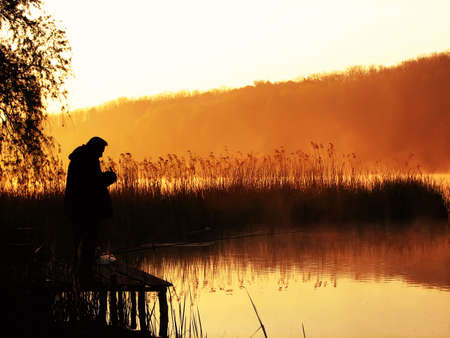 Silhouette of the fisherman on lake in rising sun beams Stock Photo