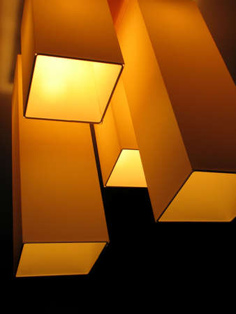 Chandelier in the form of four cubes shone by warm yellow light. Stock Photo