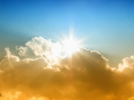 The sun and gold clouds against the blue sky