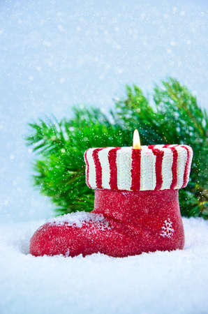 Christmas candle in form shoe on a background a spruce branch Stock Photo