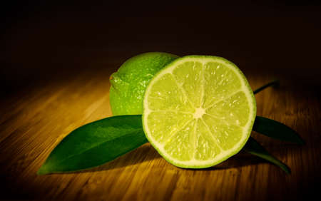 Two limes on a wooden board. Stock Photo