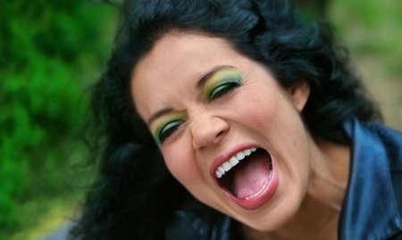 開いた口と緑と笑う女性の写真