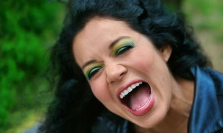 photo of woman laughing with open mouth and green  Stock Photo