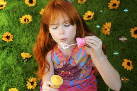 headed: Red headed girl blowing bubbles on grass with sun flowers