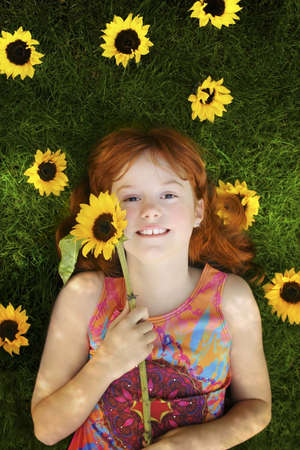 little red headed girl with sunflowers laying on grass photo