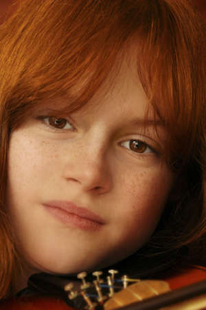 close up of red headed girl with violin Фото со стока