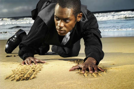 catlike: young man in suit crawling on the beach