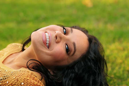 eyecontact: Latina woman smiling while laying on grass