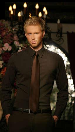 young man standing: giovane uomo in piedi con interni di lusso, vestiti di moda