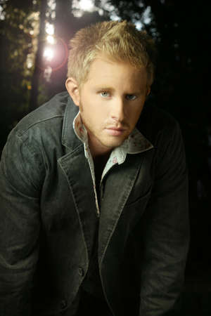 blond young man in a forest wearing a coat photo