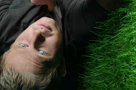 intrigue: night photo of blond guy laying on grass Stock Photo
