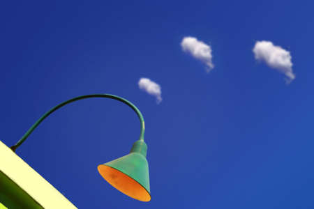 green lamp with blue sky and white clouds in the background photo