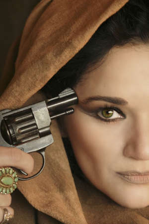 suicidal: woman pointing a gun at her own temple