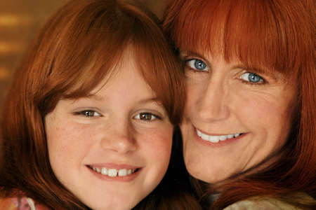 redheaded: red-headed mother and daughter smiling and hugging Stock Photo