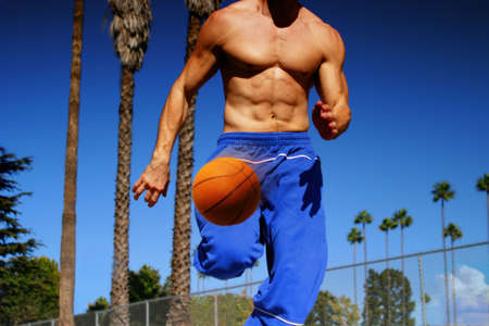 pectorals: young athlete dribbling basketball outdoors while running