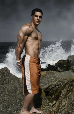 pectorals: muscular guy on the rocks by the ocean