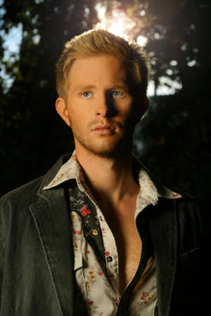 blond goodlooking young man standing in the middle of a forest with sun behind photo