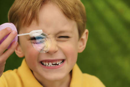 blond child putting a soap bubble in front of his right eye photo