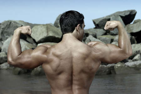 back of a bodybuilder flexing by some rocks on the beach photo