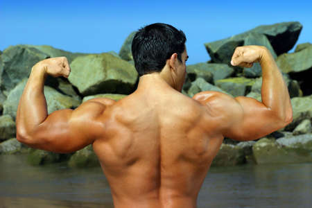 trapezius: body builder flexing his back by the ocean with rocks in the background - full color photo -