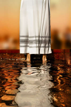 priest's ritual robes: priests white robe reflecting in baptismal font water