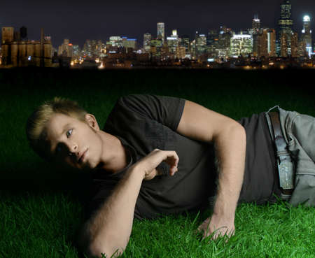 young man laying on grass with city in the background